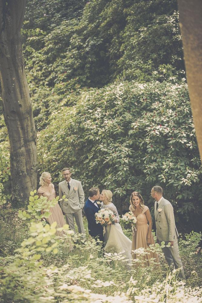 bröllopsfotograf med brudsällskapet i parken